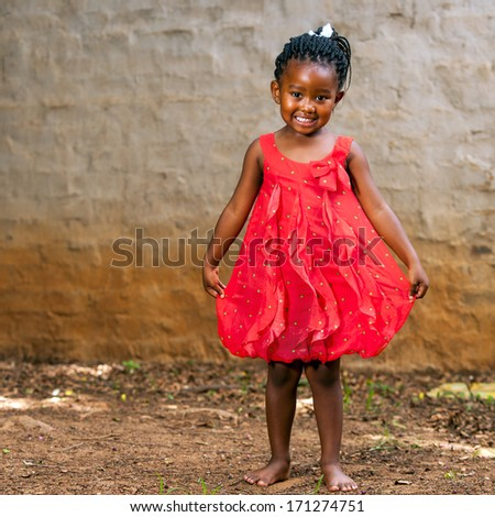 Full length portrait of cute african girl showing red dress outdoors. - stock photo