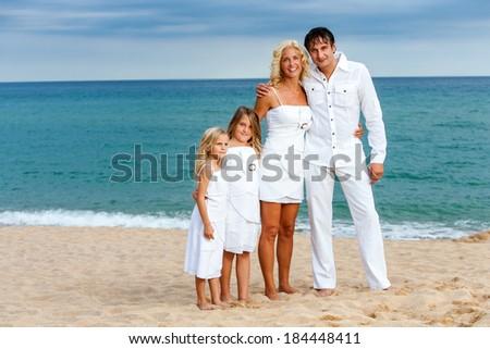 Full length portrait of cute family dressed in white on beach. - stock photo