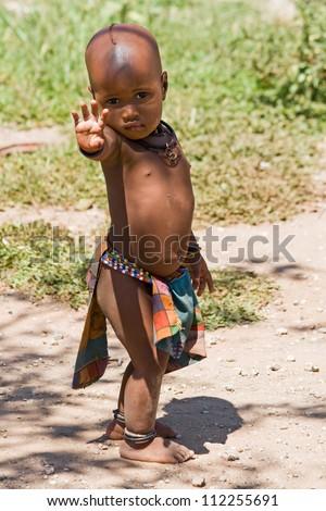 Full length portrait of cute Himba boy. - stock photo
