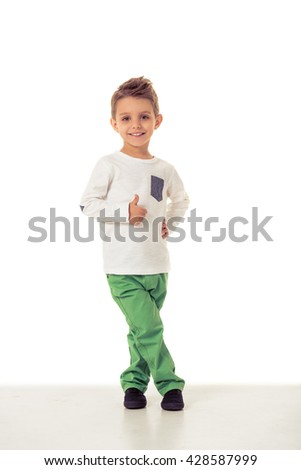 Full length portrait of cute little boy in stylish clothes showing Ok sign, looking at camera and smiling, isolated on a white background - stock photo