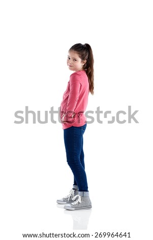 Full length portrait of cute little girl standing on white background with her hand on hip looking at camera smiling - stock photo