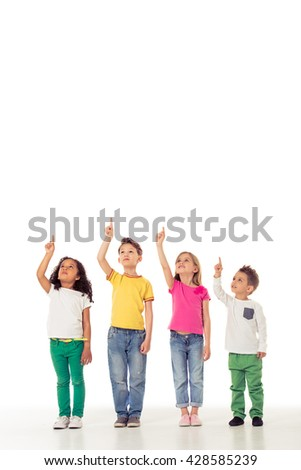 Full length portrait of cute little kids in casual clothes looking and pointing up, isolated on a white background - stock photo