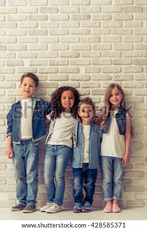 Full length portrait of cute little kids in stylish jeans clothes hugging, looking at camera and smiling, standing against white brick wall - stock photo