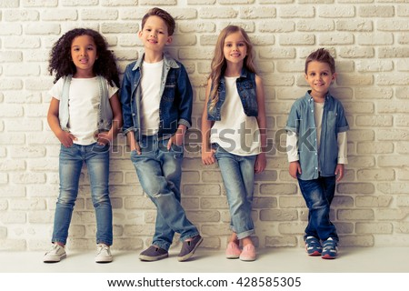 Full length portrait of cute little kids in stylish jeans clothes looking at camera and smiling, standing against white brick wall - stock photo