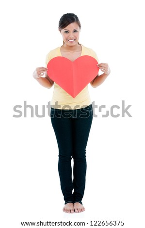 Full length portrait of cute young woman holding a heart sign over white background. - stock photo