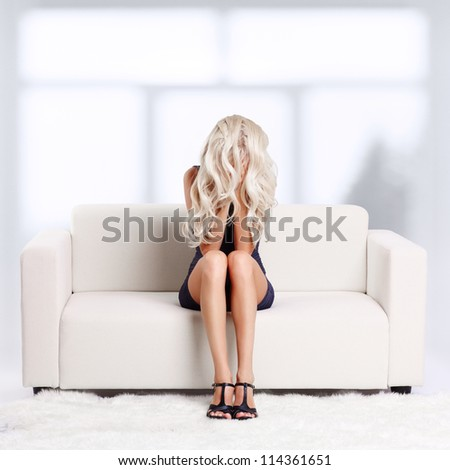 full-length portrait of depressed beautiful young blond woman sitting on couch and hiding her face in hands and hair - stock photo