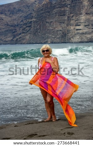 Full length portrait of elderly woman that is standing on black volcanogenic sand of Guios beach with beach wrap in hands on surf waves and cliff background in Los Gigantes, Tenerife, Canary Islands. - stock photo