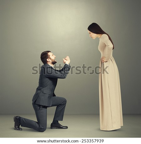 full length portrait of emotional couple over grey background. angry woman looking at man, man standing on knee and apologizing - stock photo