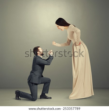 full length portrait of emotional couple over grey background. woman screaming and showing fist, man standing on knee and apologizing - stock photo