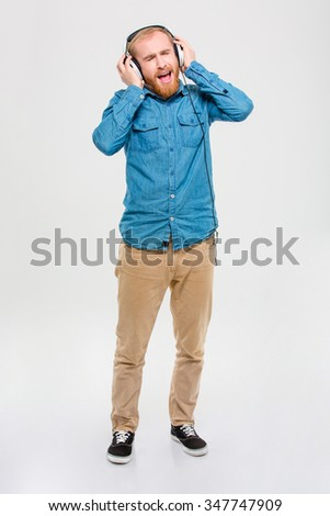 Full length portrait of excited amusing blond man with beard listening to music using headphones and singing isolated over white background - stock photo