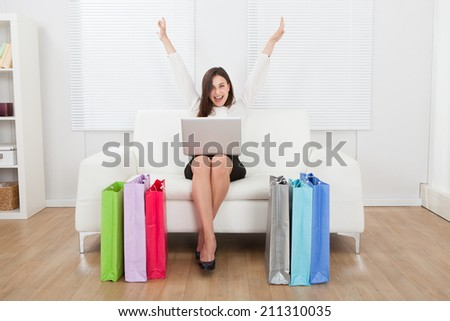 Full length portrait of excited businesswoman with laptop shopping online on sofa at home - stock photo