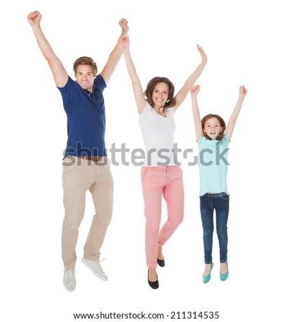 Full length portrait of excited family jumping against white background