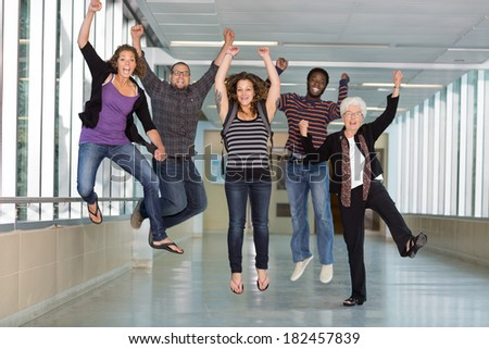 Full length portrait of excited multiethnic university students jumping in corridor with professor - stock photo
