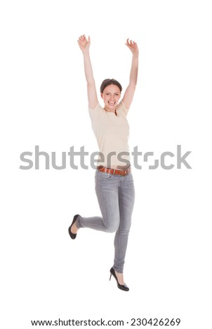Full length portrait of excited woman dancing against white background - stock photo