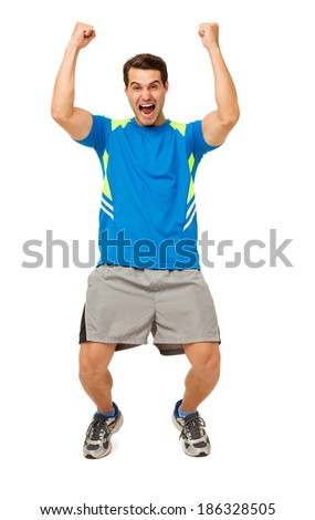 Full length portrait of excited young man in sportswear screaming with arms raised over white background. Vertical shot.