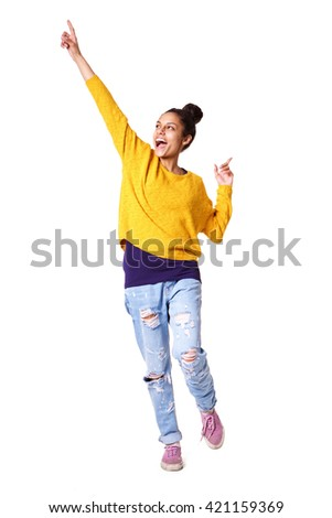 Full length portrait of excited young woman standing with her arms up on white background - stock photo