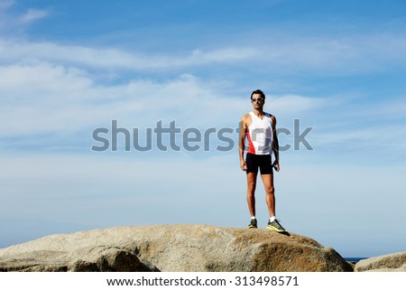 Full length portrait of exhausted male runner taking break after an active training in mountain landscape front while listening to music in headphones, mature sports man resting after active run - stock photo