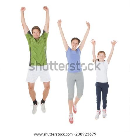 Full length portrait of family in sportswear jumping against white background - stock photo