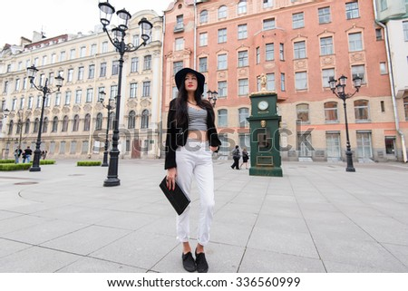Full length portrait of fashionable young woman relaxing after city walk in Saint Petersburg, attractive female model posing on the background of marvelous buildings while enjoying vacation weekends  - stock photo