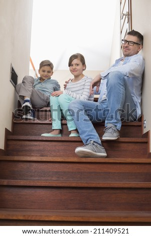 Full length portrait of father and children sitting on steps at home - stock photo