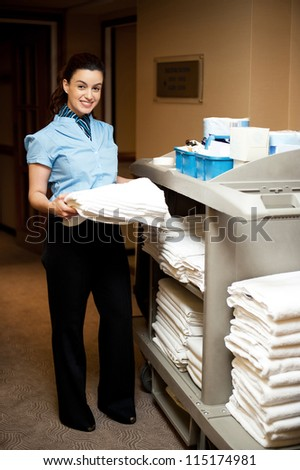 Full length portrait of female executive holding bath towel and standing beside the housekeeping cart - stock photo