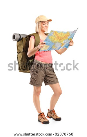 Full length portrait of female hiker looking at map isolated on white background - stock photo