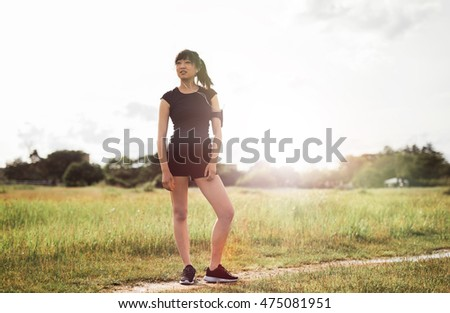 Full length portrait of female runner standing outdoors in morning. Chinese female model in sports wear ready for running workout.