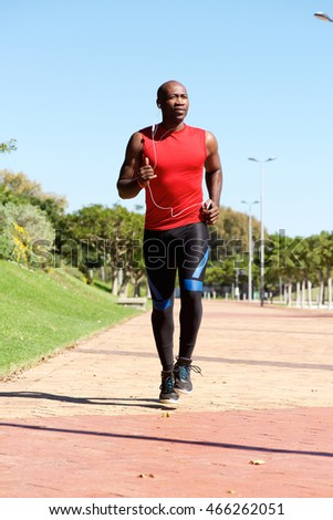 Full length portrait of fit exercising man running outside at the park