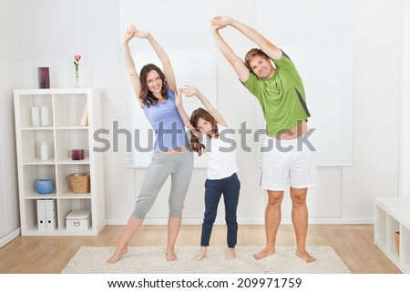 Full length portrait of fit family performing yoga at home - stock photo