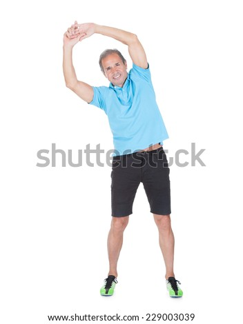 Full length portrait of fit mature man exercising against white background - stock photo
