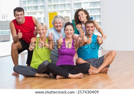 Full length portrait of fit men and women gesturing thumbs up in fitness studio - stock photo