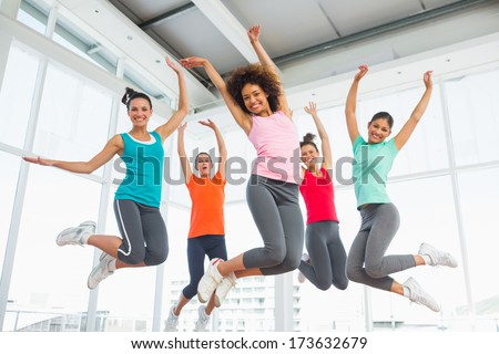 Full length portrait of fitness class and instructor jumping in fitness studio - stock photo