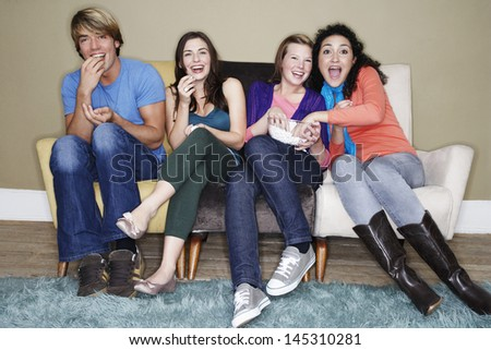 Full length portrait of four friends eating popcorn while watching movie on sofa - stock photo