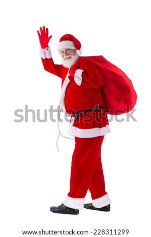 Full-length portrait of friendly Santa with a sack of presents - stock photo