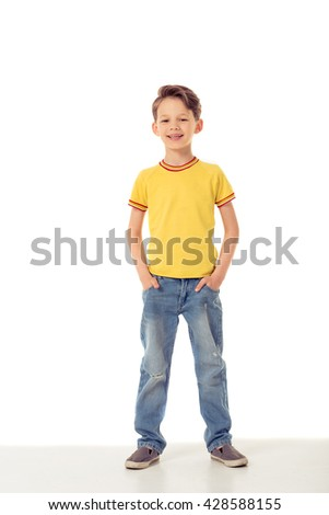 Full length portrait of funny little boy looking at camera and smiling while standing with hands in pockets, isolated on a white background - stock photo