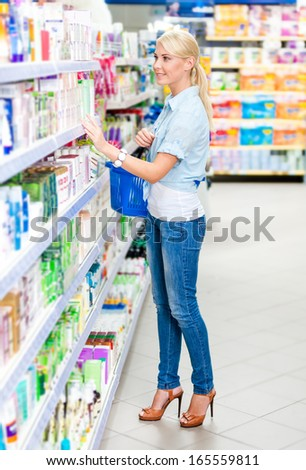 Full length portrait of girl at the shop choosing cosmetics among the great variety of products. Concept of consumerism, retail and purchase - stock photo
