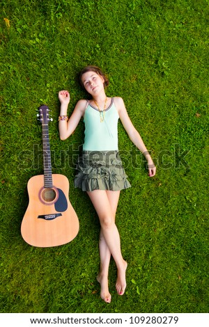 Full length portrait of girl lying down on grass in the park with a guitar - stock photo