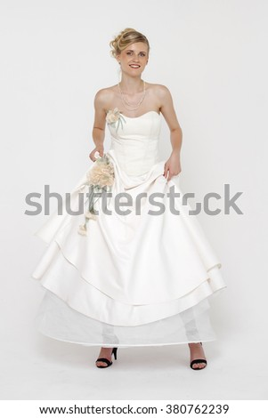 Full length portrait of gorgeous bride wearing wedding dress over grey background