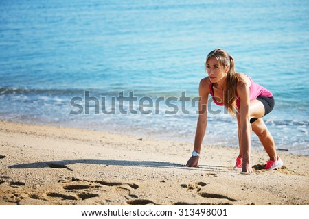 Full length portrait of gorgeous female runner with beautiful figure preparing for jogging on the beach while stretching legs muscles,  young fit woman doing an active exercise outdoors at seashore - stock photo