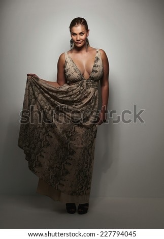 Full length portrait of gorgeous young lady in beautiful evening gown. Oversized female model posing on grey background. - stock photo