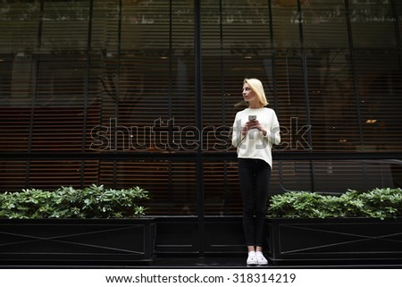 Full length portrait of gorgeous young woman holding smart phone in the hand and looking to the empty copy space area for text message or information, female hipster have chat conversation on phone - stock photo