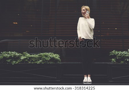 Full length portrait of gorgeous young woman talk on smart phone while looking to the empty copy space area for text message or information,female hipster at mobile phone conversation,filter image - stock photo