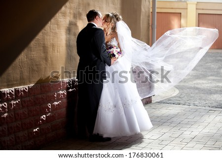 Full length portrait of groom hugging bride while wind lifting veil