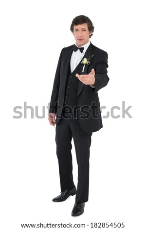 Full length portrait of groom in tuxedo offering hand over white background