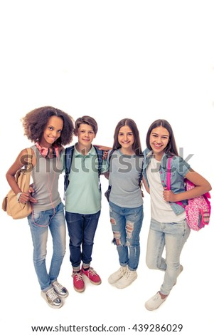 Full length portrait of group of teenage boys and girls with school backpacks looking at camera and smiling, standing, isolated on white - stock photo