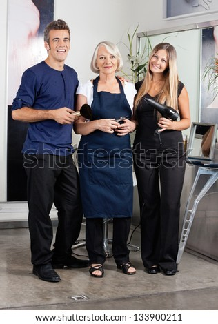 Full length portrait of hairstylists holding scissors - stock photo