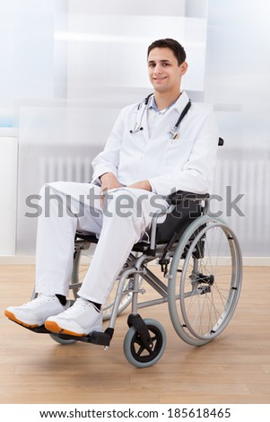 Full length portrait of handicapped doctor sitting on wheel chair in hospital - stock photo
