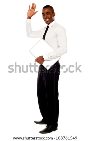 Full length portrait of handsome african businessman waving hand and holding laptop