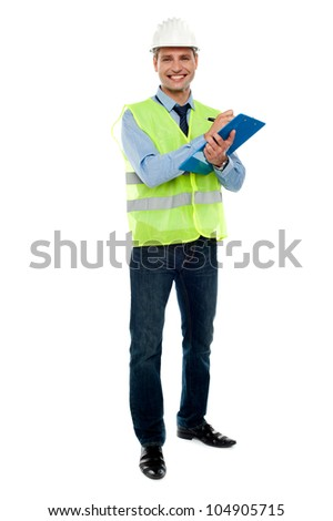 Full length portrait of handsome architect writing key notes on clipboard