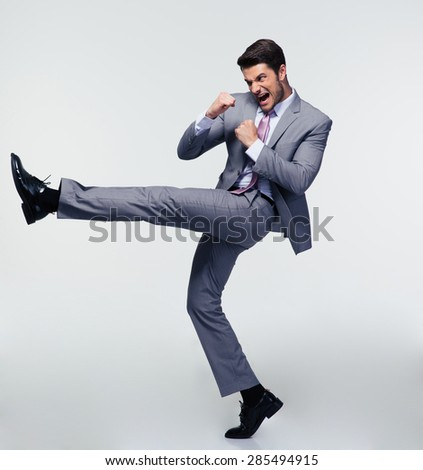 Full length portrait of handsome businessman kicking over gray background - stock photo